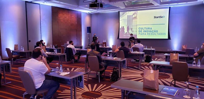Foto de uma edição presencial do evento; pessoas com máscara, sentadas; palestrantes no palco