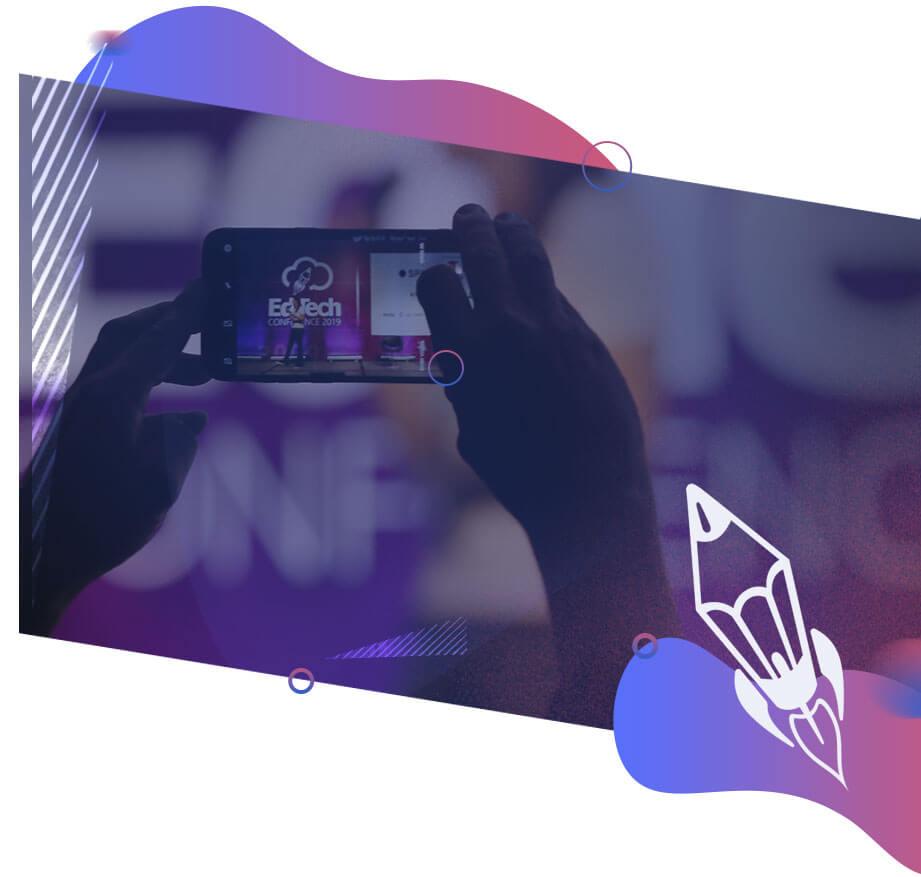 Imagem de uma mão segurando um celular que está filmando o evento EdTech 2019, ícone de um foguete de lápis branco.