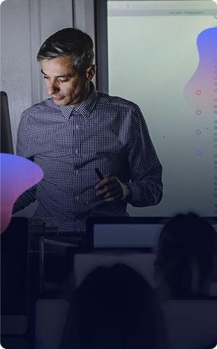 Imagem de um professor segurando os óculos e uma caneta, projetor ao fundo