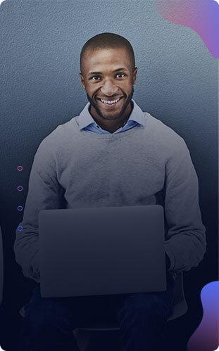 Imagem de um homem sorrindo segurando um laptop no colo