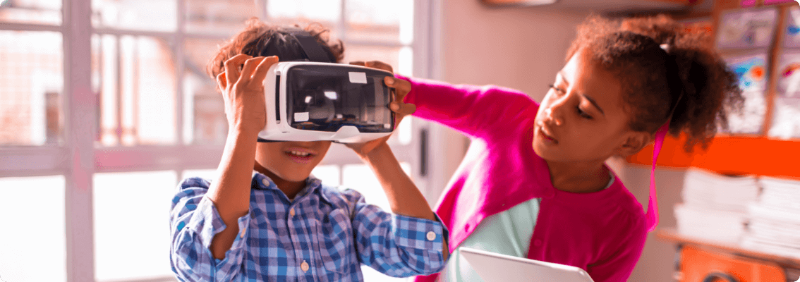 Foto duas crianças, um menino e uma menina, o menino esta colocando o óculos vr enquanto a menina o ajuda