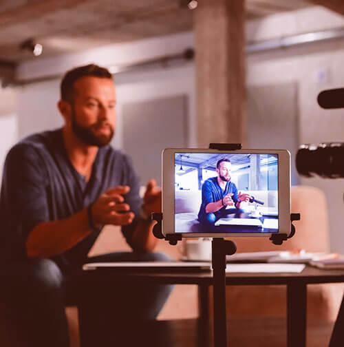 Foto de um homem com barba sentado sendo gravado por uma câmera