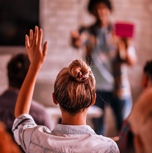 Foto de uma mulher loira de costas levantando a mão encenando como tivesse tirando uma dúvida