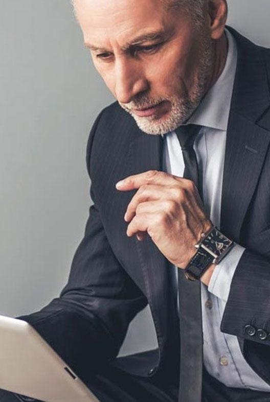 Imagem de um homem de terno cinza mexendo em um tablet