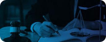 Foto de uma mão escrevendo com uma caneta em um livro, uma balança pequena e um martelo de juiz.