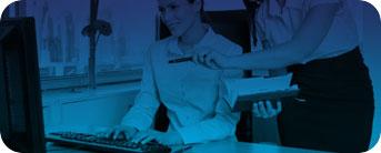 Foto de uma mulher de roupa social, apontando com uma caneta em uma das mãos para o computador, onde tem um homem sentado digitando.