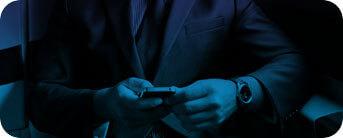 Foto de um homem de terno segurando um celular
