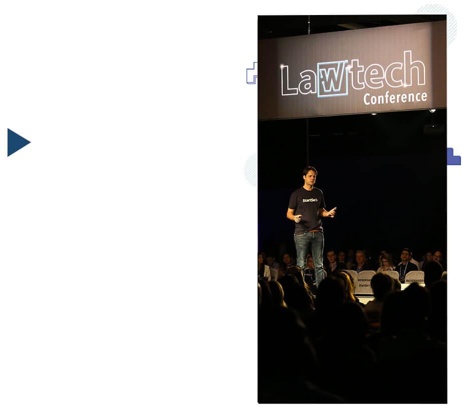 Pedro Englert palestrando no palco e ao fundo logo do Lawtech