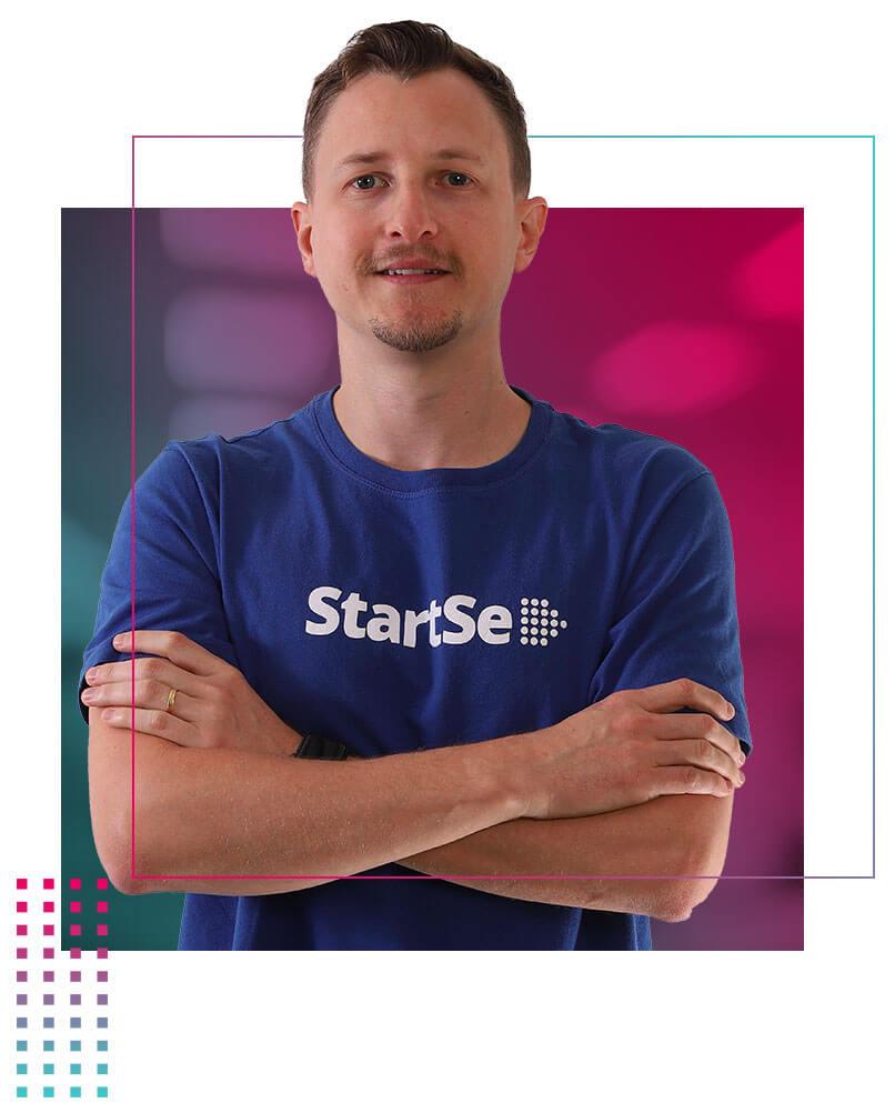 Marcelo Pimenta com camiseta azul da StartSe e braços cruzados
