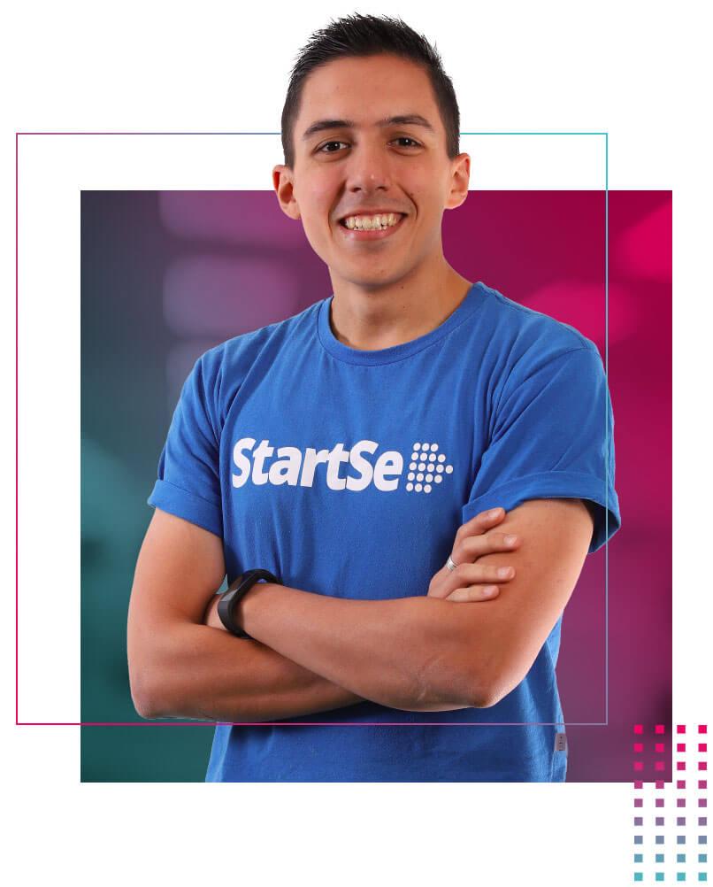 Matheus Bellini com camiseta azul da StartSe e braços cruzados