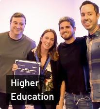Da esquerda para direita: Junior Borneli, mulher participante do Power Class, Rony Meisler e Gustavo Caetano; todos de pé e sorrindo; texto 'Higher Education' abaixo