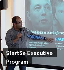 Cristiano Kruel apontando com braço esquerdo para quadro branco; segurando microfone com braço direito; de pé; texto 'StartSe Executive Program' abaixo
