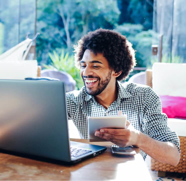 Homem sorrindo, segurando tablet; camisa xadrez; olhando para notebook; notebook em cima da mesa; natureza ao fundo