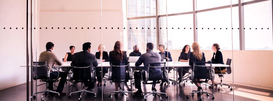 Mesa de reunião com muitas pessoas conversando entre elas