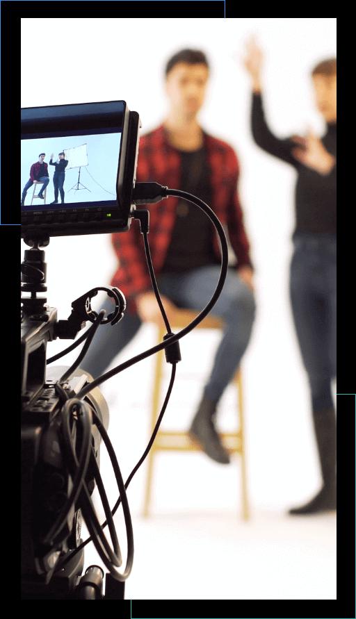 Parte de uma câmera ao lado esquerdo, com foco; fundo desfocado com uma pessoa sentada num banco e outra de pé com o braço direito levantado