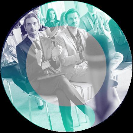 Um circulo com a imagem de um grupo de pessoas sentadas aplaudindo.
